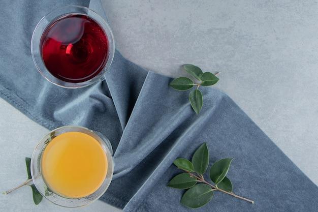 Twee glazen sap en bladeren op een handdoek, op de marmeren achtergrond. hoge kwaliteit foto
