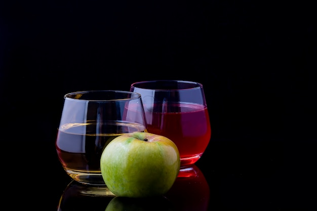 Twee glazen sap en een appel op een zwarte achtergrond.