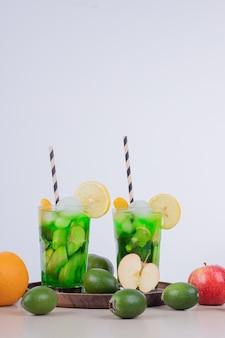 Twee glazen sap met fruitplakken en vers fruit op witte muur.