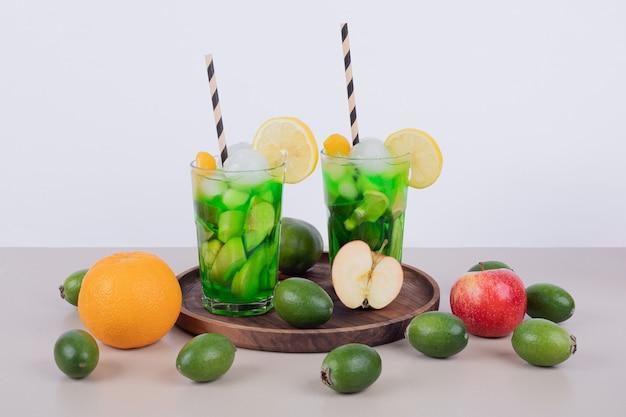 Twee glazen sap met plakjes fruit en vers fruit.