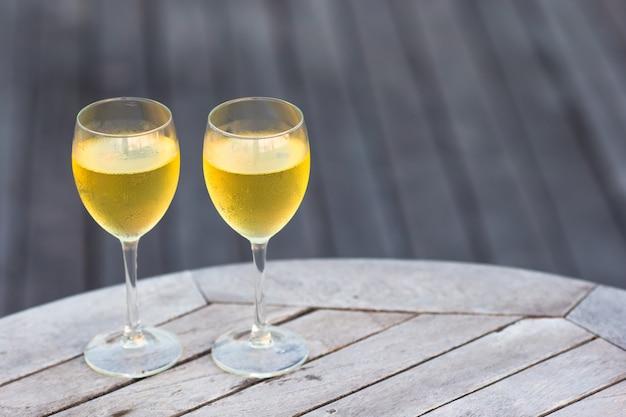 Twee glazen smakelijke witte wijn bij zonsondergang op houten lijst
