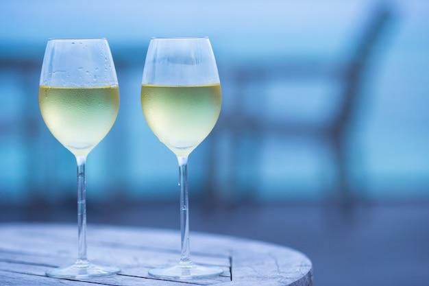 Twee glazen smakelijke witte wijn bij zonsondergang
