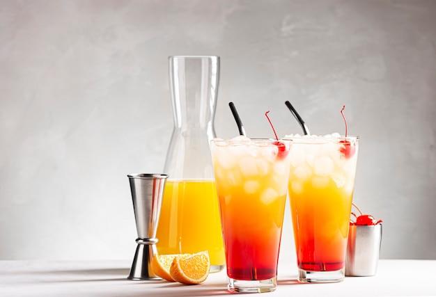 Twee glazen tequila sunrise cocktail op een grijze betonnen tafel naast een karaf sap