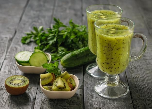 Twee glazen vers gemaakte kiwi en komkommer smoothies op een zwarte houten tafel