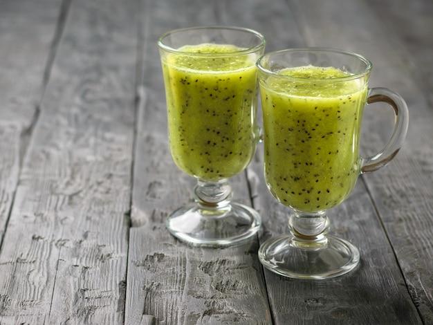 Twee glazen vers gemaakte kiwi met komkommer smoothies op een zwarte houten tafel