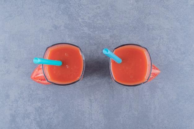 Twee glazen vers tomatensap en tomaten op een grijze achtergrond.