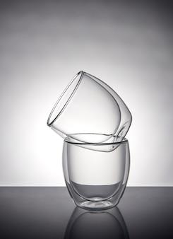 Twee glazen voor koffie of thee, staande op elkaar op een grijs met reflectie