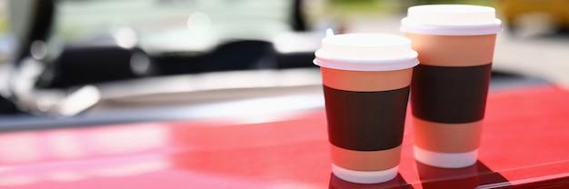 Twee glazen warme drank staan op de auto. levering van eten en drinken concept