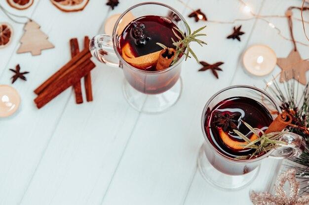 Twee glazen warme glühwein met rozemarijn op een witte plaat in de sfeer van een nieuwjaar. bovenaanzicht,