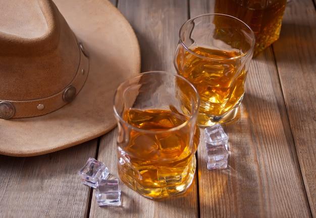 Twee glazen whisky en cowboyhoed op de houten lijst.