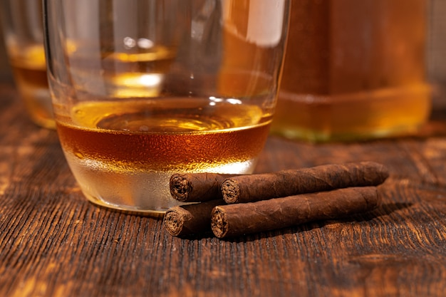 Twee glazen whisky en sigaren op houten tafel