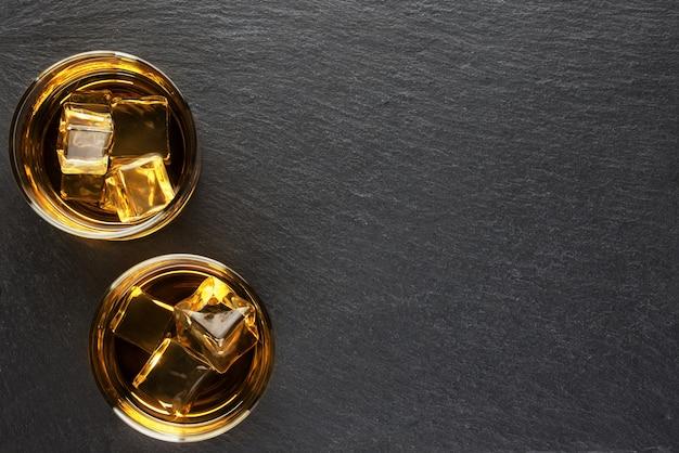 Twee glazen whisky met ijs op zwart