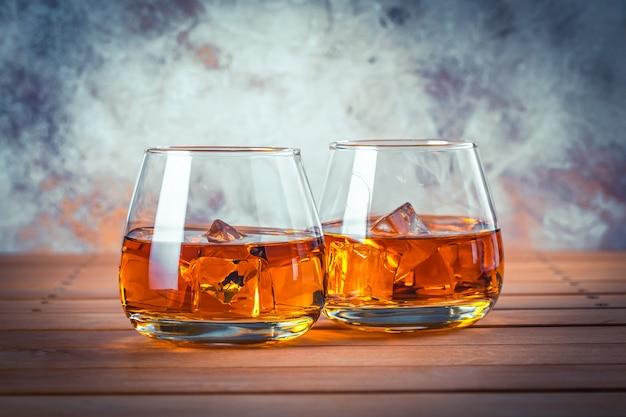 Twee glazen whisky met ijs. stilleven. brandy, bourbon op een bruin houten tafel. sterke alcoholische drank. rum, whisky.