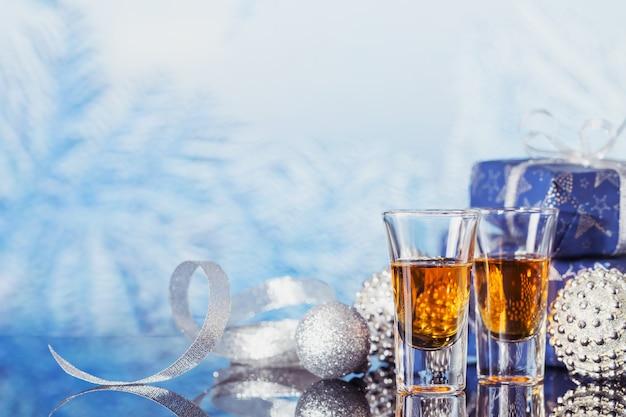Twee glazen whisky of bourbon met kerstversiering op een lichte bokeh