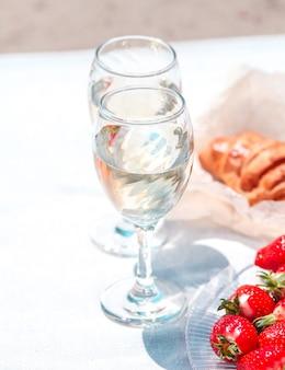 Twee glazen wijn, aardbeien en brood op een picknick op het zand