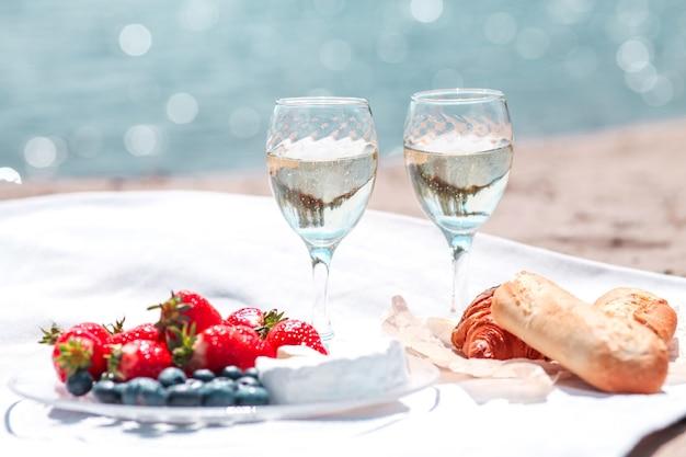 Twee glazen wijn, aardbeien, kaas, bosbessen en brood op een picknick op het strand