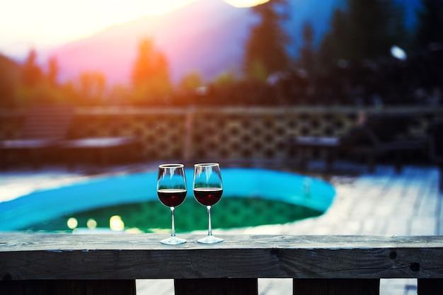 Twee glazen wijn bij dramatische zonsonderganghemel op de achtergrond van het berglandschap