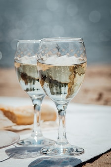 Twee glazen wijn en brood tijdens een picknick op het strand