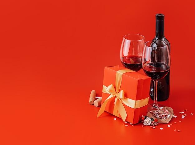 Twee glazen wijn en een cadeau in een luxe doos