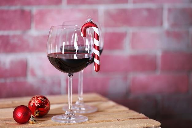 Twee glazen wijn met kerstmisspeelgoed op muurachtergrond