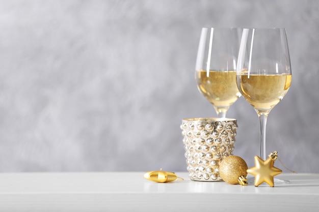 Twee glazen wijn met kerstspeelgoed op grijze muurachtergrond