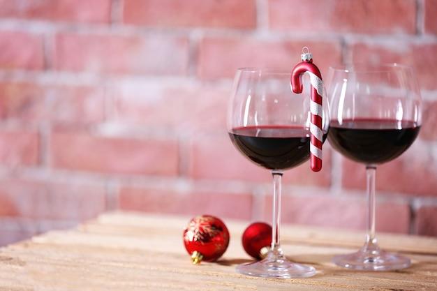 Twee glazen wijn met kerstspeelgoed op muuroppervlak