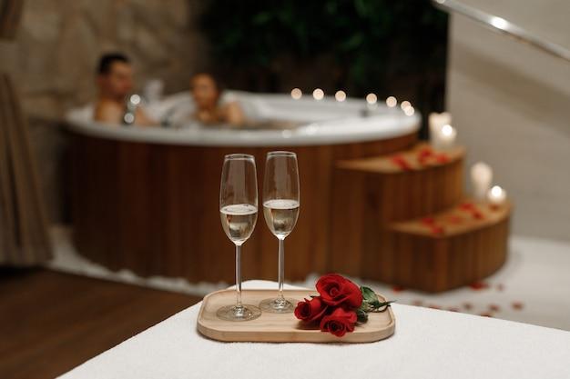 Twee glazen wijn op de ruimte van een paar dat een bad neemt