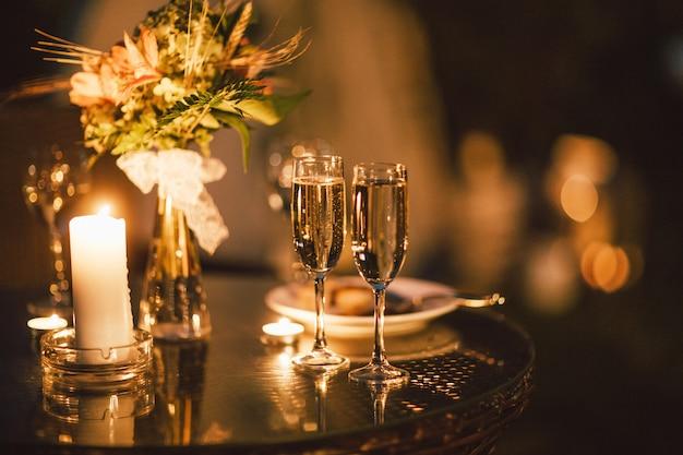 Twee glazen wijn op lijst aangaande de achtergrond van huwelijksboeket, avond, eind van gebeurtenis