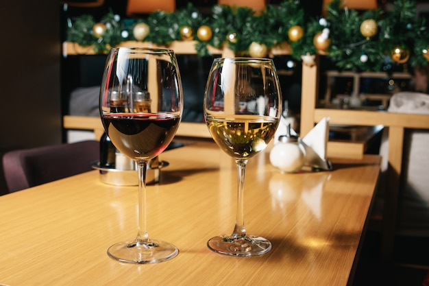 Twee glazen wijn witte en rode status op een lijst met kaars in het zonlicht