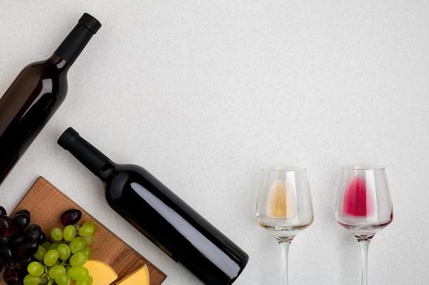 Twee glazen witte en rode wijn kaas en druiven bovenaanzicht