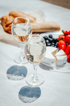 Twee glazen witte wijn en bessen, gebak, brood en camembert kaas op witte tafel opgezet