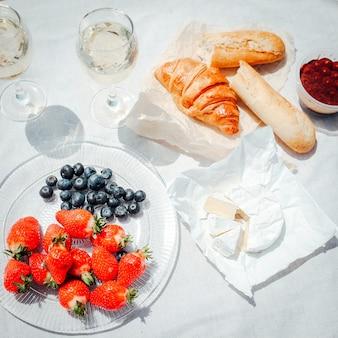 Twee glazen witte wijn en bessen, gebak, brood en camembert kaas op witte tafel set-up