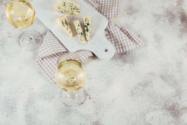 Twee glazen witte wijn geserveerd met kaasplankje op een witte ondergrond. wijn stemming concept.