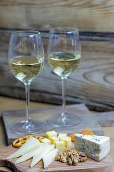 Twee glazen witte wijn met kaasplank op rustieke met verschillende kaas, blauwe kaas, gauda en noten en snacks