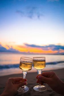 Twee glazen witte wijn op het strand bij zonsondergang