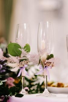 Twee glazen zijn versierde bloemen met linten.
