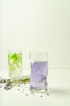 Twee glazen zomer verfrissende drankjes, lavendel limonade en komkommer doordrenkt met water