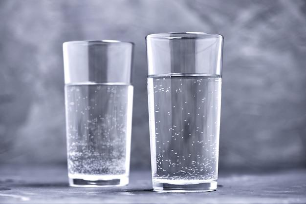 Twee glazen zuiver water op onscherpe achtergrond