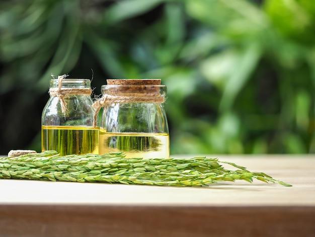 Twee glazenflessen rijstzemelenolie in groen zonlicht