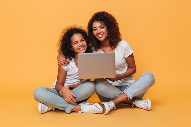 Twee glimlachende afro amerikaanse zusters die laptop computer houden