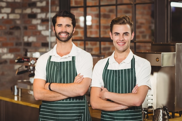 Twee glimlachende baristas die de camera bekijken