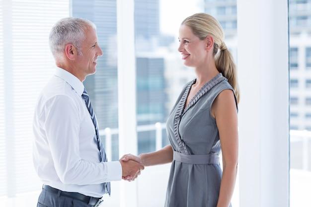 Twee glimlachende bedrijfsmensen die handen schudden