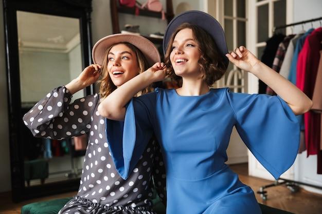 Twee glimlachende geweldige jonge vrouwen die hoeden dragen.