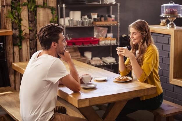 Twee glimlachende hipsters die koffie drinken