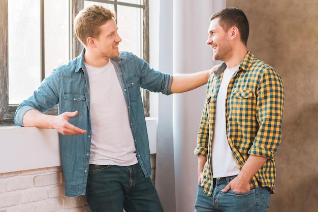 Twee glimlachende jonge mannen die aan elkaar spreken
