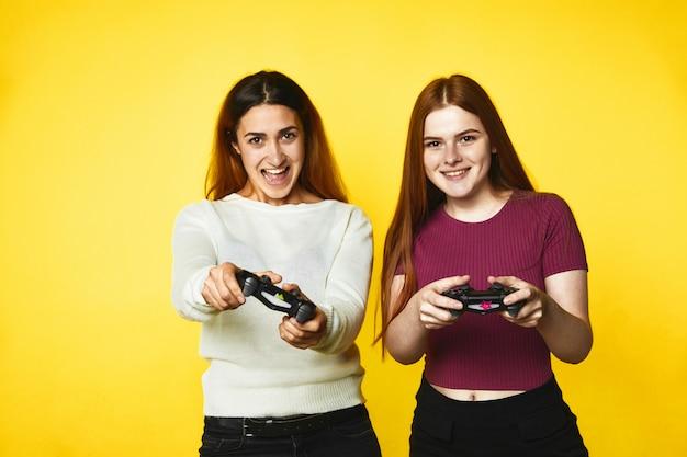 Twee glimlachende kaukasische meisjes met draadloze joystick