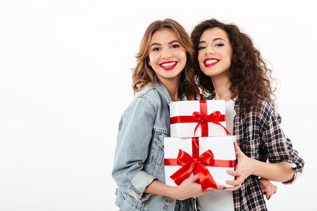 Twee glimlachende meisjes die met giften over witte muur stellen