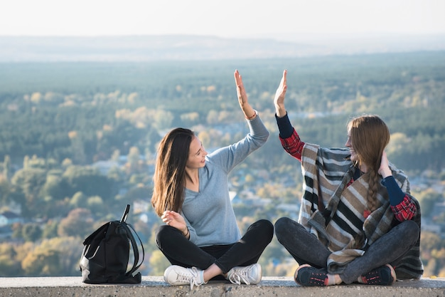 Twee glimlachende meisjes die pretzitting op een heuvel hebben. zonnige dag