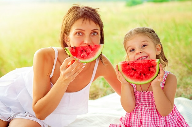 Twee glimlachende meisjes eet in openlucht plak van watermeloen op weide. moeder en dochter brengen samen tijd door. dieet, vitamines, gezond voedselconcept
