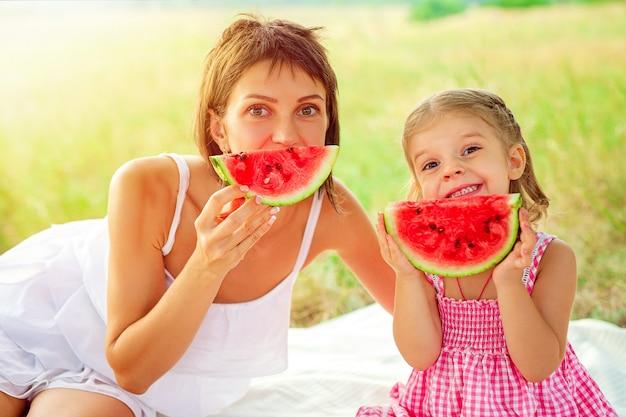 Twee glimlachende meisjes eet in openlucht plak van watermeloen op weide. moeder en dochter brengen samen tijd door. dieet, vitamines, gezond voedselconcept.